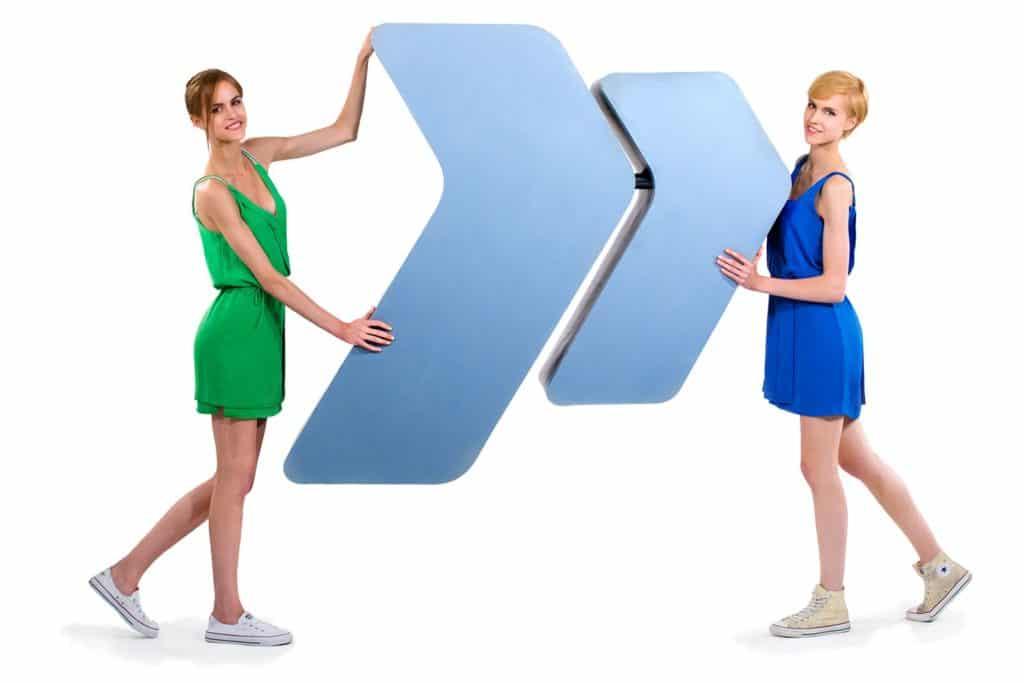 Zwei Frauen im Kleid halten ein Logo in der Hand