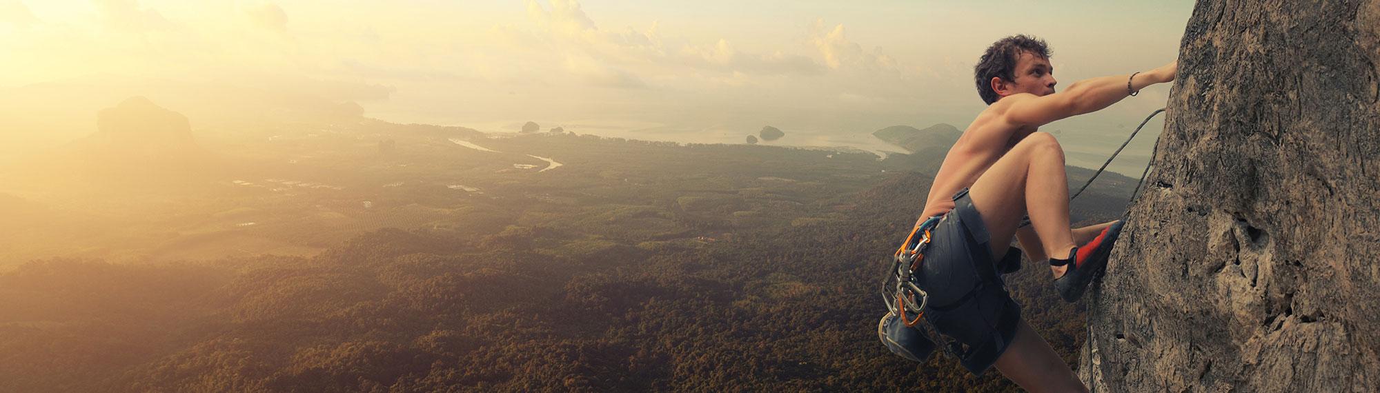 Männlicher Felskletterer klettert mit atemberaubender Landschaft den Fels hinauf