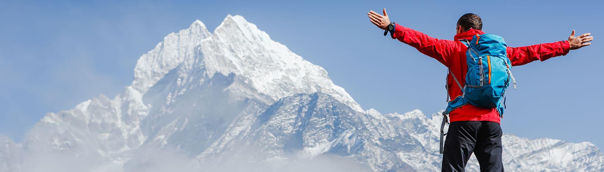 Wanderer mit Rucksack steht vor einem Berg und breitet die Arme aus