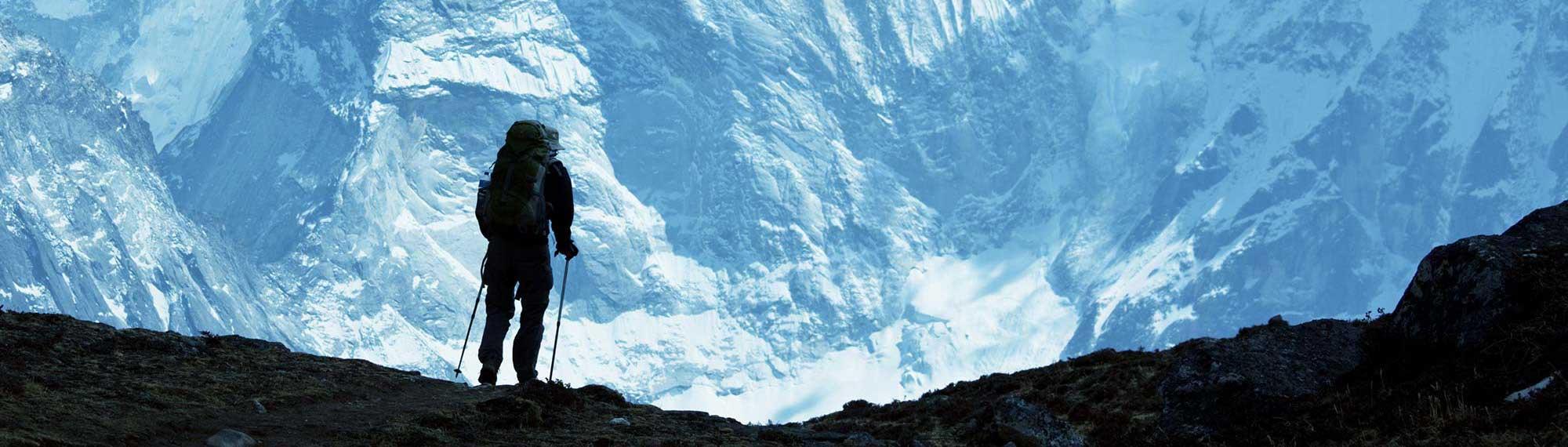 Panorama von einem Bergsteiger vor einer schneebedeckten Felslandschaft