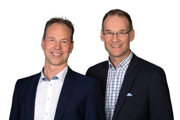 Zwei Männer im Anzug stehen nebeneinander