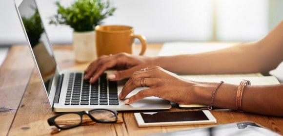Frau mit Schmuck bedient Tastatur am Laptop