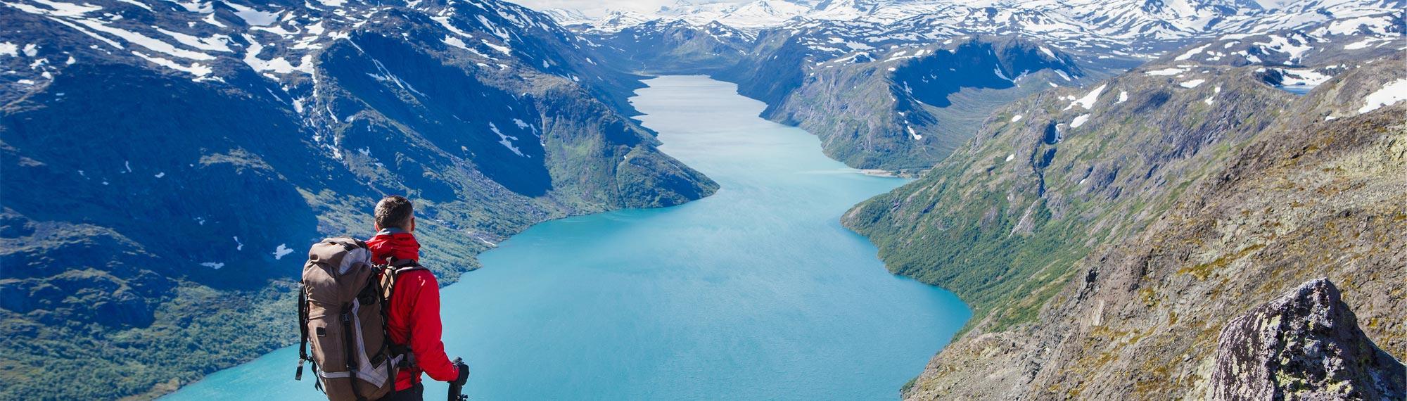 Wanderer genießt Ausblick auf See und Berge